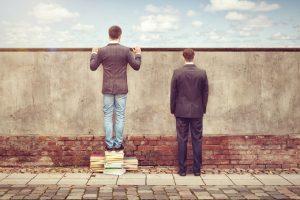 une personne qui regarde au-dessus d'un mur; symbolise l'étude de concurrence